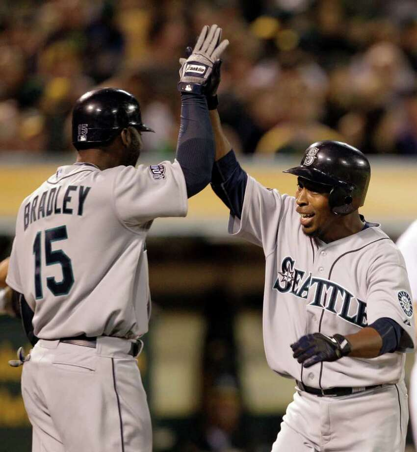 Seattle Mariners' Chone Figgins, right, celebrates with teammate Milton Bradley (15) after Figgins hit a home run off Oakland Athletics' Craig Breslow during the seventh inning of a baseball game Friday, April 1, 2011, in Oakland, Calif.