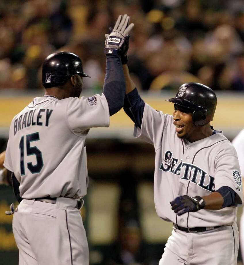 Seattle Mariners' Chone Figgins, right, celebrates with teammate Milton Bradley (15) after Figgins hit a home run off Oakland Athletics' Craig Breslow during the seventh inning of a baseball game Friday, April 1, 2011, in Oakland, Calif. Photo: AP