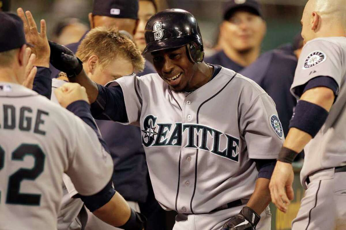 Seattle Mariners' Chone Figgins, right, celebrates upon returning to the dugout after hitting a home run off Oakland Athletics' Craig Breslow during the seventh inning of a baseball game Friday, April 1, 2011, in Oakland, Calif.