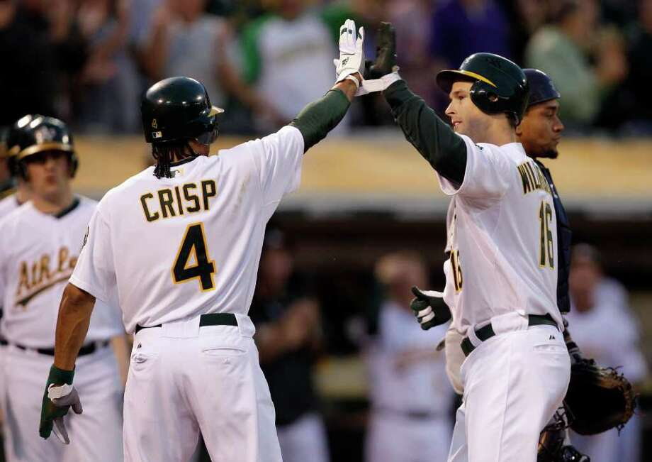Oakland Athletics' Josh Willingham, right, is congratulated by teammate Coco Crisp (4) after Willingham hit a two run home run off Seattle Mariners' Felix Hernandez during the first inning of a baseball game Friday, April 1, 2011, in Oakland, Calif. Photo: AP