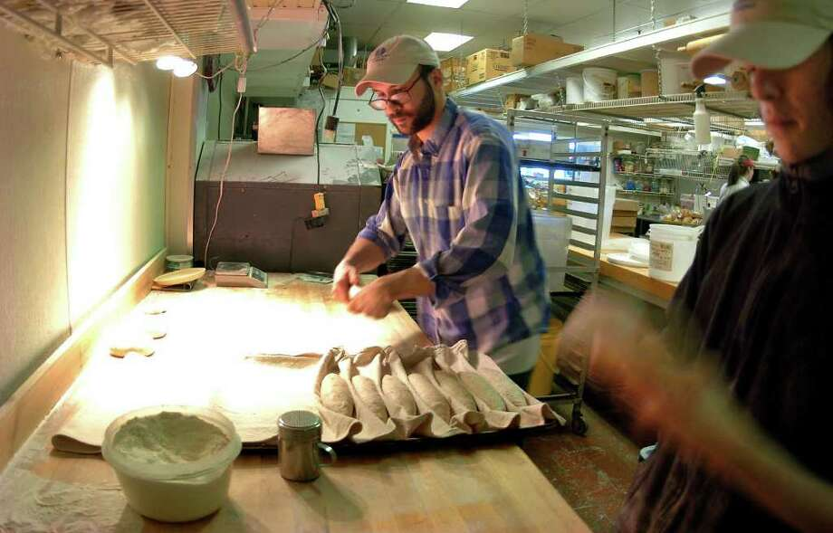 Fairfield Bread Company owner Michael Mordecai, center, and his helper Benjamin Popalardo work on a batch of his unique baquette style bread he calls The Flaxette, at Adams Bakery in Fairfield, Conn. on Saturday April 2, 2011. Mordecai rents the space in the bakery to make his bread which features organic flax seed. Photo: Christian Abraham / Connecticut Post