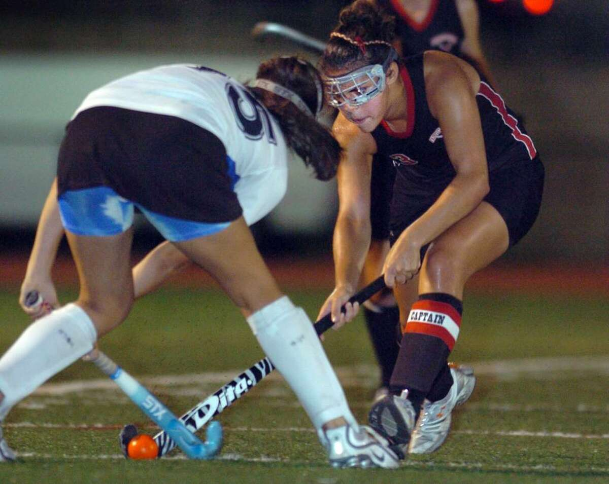 Fairfield Warde's Christie Zierolf, right, and Fairfield Ludlowe's Stephanie Gorab battle for the ball during the second half of Tuesday night's field hockey game at Ludlowe.