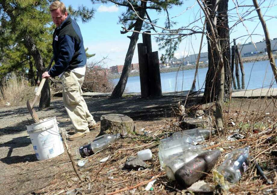 Chris German, Connecticut Community Boating (CCB) executive director, shovels broken glass along Bridgeport Harbor Saturday, April 2, 2011.  CCB received special permision to clean up the area though they are still waiting for approval to use the spot for the group's new home. Photo: Autumn Driscoll / Connecticut Post