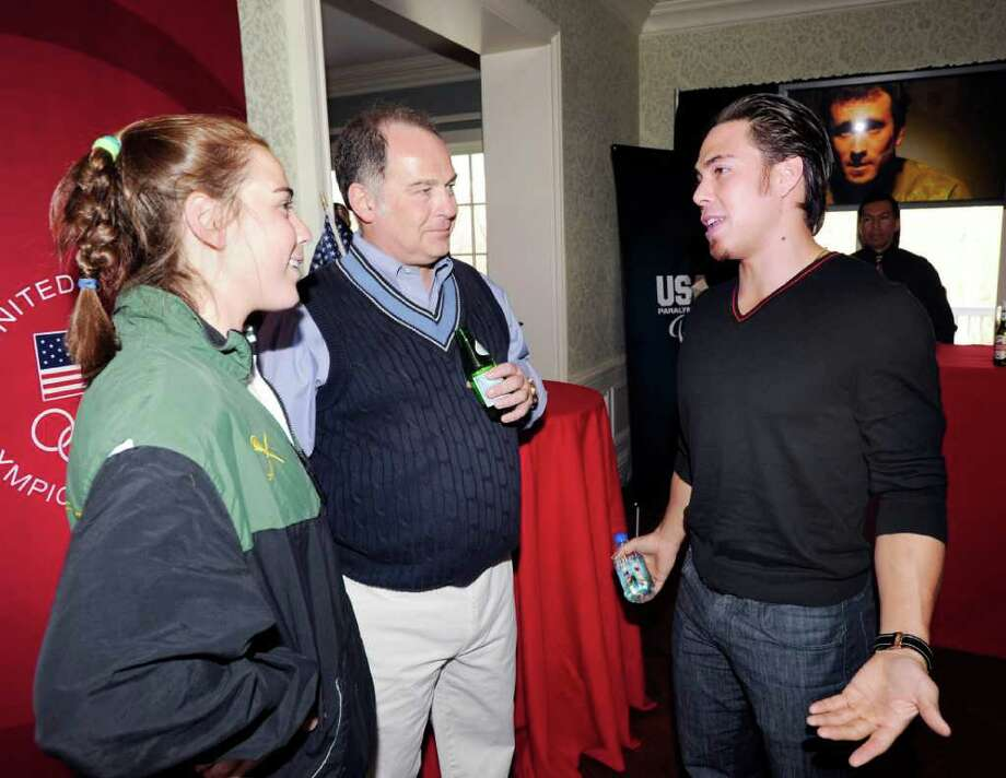 From left, Parker Procida and her father, Mario, speak with Apolo Anton Ohno, an American short-track speedskating gold medalist in the 2002 and 2006 Winter Olympics, during a U.S. Olympic Committee exclusive donor reception at the Greenwich home of the Procidas, Saturday night, April 2, 2011.  Mario's wife is Perri S. Procida, who is  a U.S. Olympic Foundation trustee. Photo: Bob Luckey / Greenwich Time