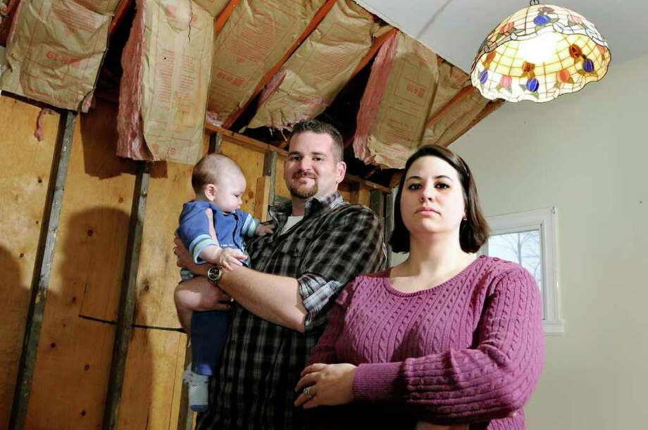 Anthony and Bridget Canfield, along with their 6-month-olc son A.J., stand in the water-damaged dining room on Thursday, March 31, 2011, at their home in Averill Park, N.Y. (Cindy Schultz / Times Union) Photo: Cindy Schultz