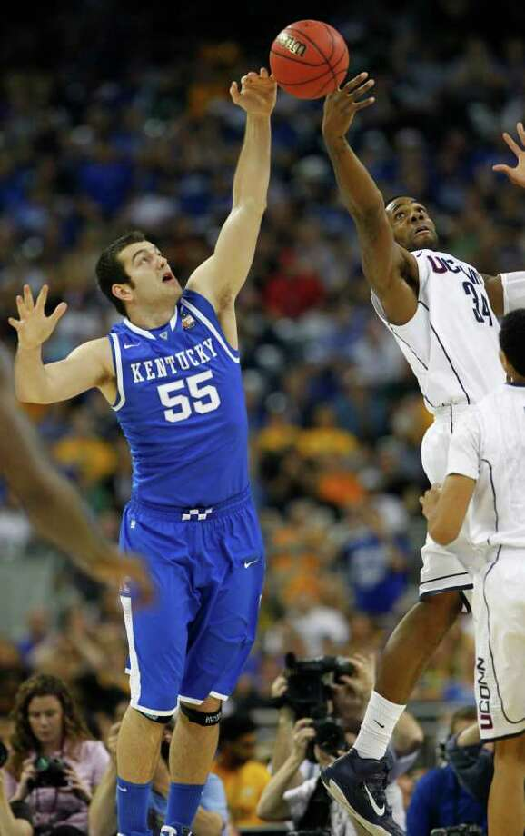 Kentucky forward Josh Harrellson (55) and Connecticut center Alex Oriakhi (34) fight for a rebound during the first half of the NCAA National Semifinals at Reliant Stadium on Saturday, April 2, 2011, in Houston.  ( Nick de la Torre / Houston Chronicle ) Photo: Nick De La Torre, Houston Chronicle For The Connecticut Post / Houston Chronicle for the Connecticut Post