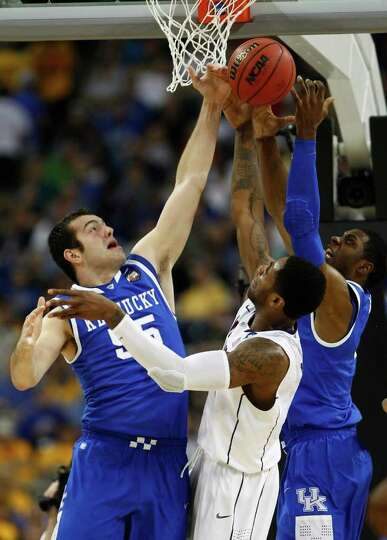 Kentucky forward Josh Harrellson (55) fights for a rebound with Connecticut center Alex Oriakhi (34)