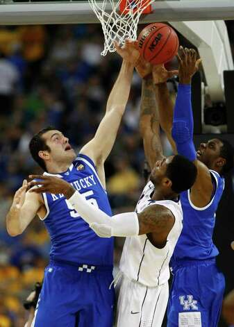 Kentucky forward Josh Harrellson (55) fights for a rebound with Connecticut center Alex Oriakhi (34) and Kentucky forward Terrence Jones (3) during the first half of the NCAA National Semifinals at Reliant Stadium on Saturday, April 2, 2011, in Houston.  ( Nick de la Torre / Houston Chronicle ) Photo: Nick De La Torre, Houston Chronicle For The Connecticut Post / Houston Chronicle for the Connecticut Post