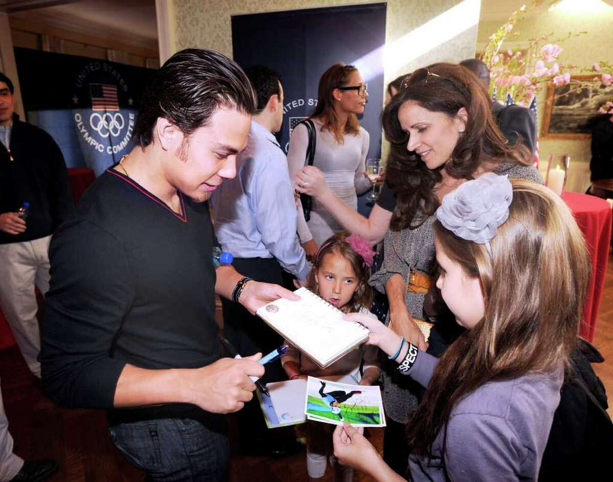 At left, Apolo Anton Ohno, an American short-track speed skating gold medalist in the 2002 and 2006 Winter Olympics, signs autographs for Margaret Schaftel, right, of Greenwich and her two daughters, Mia, lower right, 9, and Ella, 6, during a U.S. Olympic Committee exclusive donor reception at the Greenwich home of U.S. Olympic Foundation Trustee Perri S. Procida and her husband, Mario, Saturday night, April 2, 2011. In the background at center is Lori