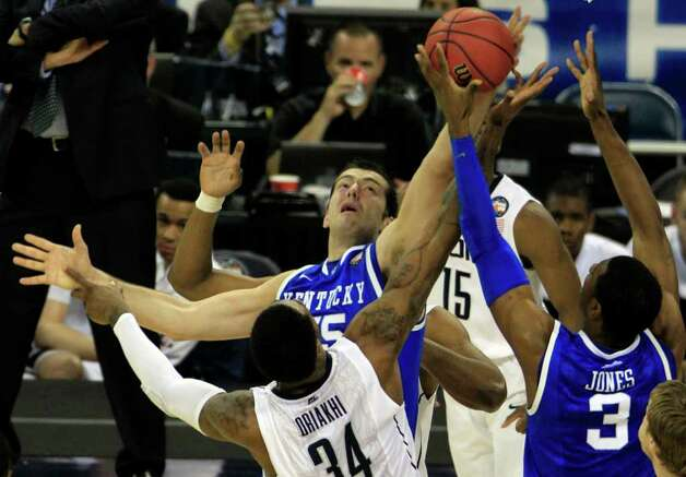 Kentucky forward Josh Harrellson (55) and Kentucky forward Terrence Jones (3) battle for a rebound against Connecticut center Alex Oriakhi (34) during the first half of the NCAA National Semifinals at Reliant Stadium on Saturday, April 2, 2011, in Houston.  ( Brett Coomer / Houston Chronicle ) Photo: Brett Coomer, Houston Chronicle For The Connecticut Post / Houston Chronicle for the Connecticut Post