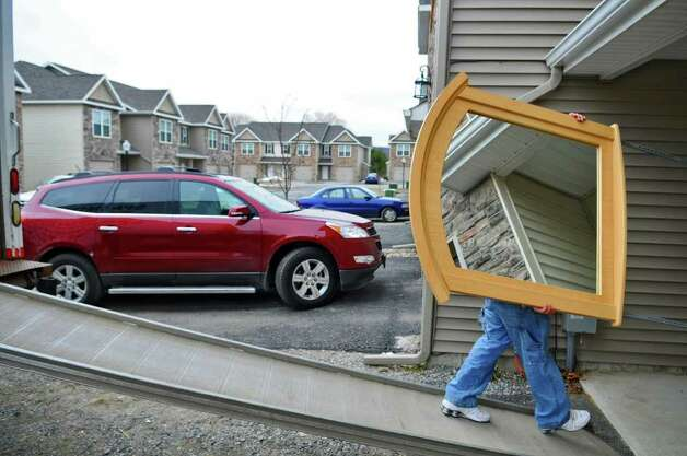 Vincent Nichols, owner of Spa Moving Co. of Saratoga Springs, carries a mirror into a unit at the Ridge View Town Homes while moving a client on Thursday, March 31, 2011 in Wilton, NY.  He says the company, which has been in business since 1974, is busy six days a week. ( Philip Kamrass/ Times Union ) Photo: Philip Kamrass
