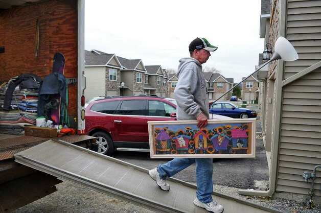Mike Maki of Saratoga Springs, an employee of Spa Moving Co. of Saratoga Springs, carries a lamp and a framed picture into a unit at the Ridge View Town Homes on Thursday, March 31, 2011, in Wilton, NY. Owner Vincent Nichols says the company, which has been in business since 1974, is busy six days a week. ( Philip Kamrass/ Times Union ) Photo: Philip Kamrass