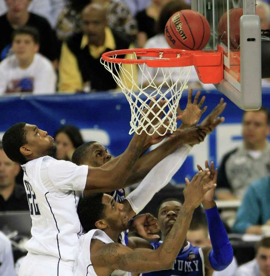 Connecticut forward Roscoe Smith (22) (left) Connecticut center Alex Oriakhi (34) (below) Kentucky forward Terrence Jones (3) (right) and Kentucky guard Darius Miller (1) battle for the ball on UConn's rim during the second half of the NCAA National Semifinals at Reliant Stadium on Saturday, April 2, 2011, in Houston.  ( Brett Coomer / Houston Chronicle ) Photo: Brett Coomer, Houston Chronicle For The Connecticut Post / Houston Chronicle for the Connecticut Post