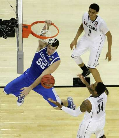 Kentucky forward Josh Harrellson (55) dunks the ball next to Connecticut center Alex Oriakhi (34) and Connecticut forward Jeremy Lamb (3) during the second half of the NCAA National Semifinals at Reliant Stadium on Saturday, April 2, 2011, in Houston.  UConn defeated 56-55 and will play Butler in the National Championship game. ( Nick de la Torre / Houston Chronicle ) Photo: Nick De La Torre, Houston Chronicle For The Connecticut Post / Houston Chronicle for the Connecticut Post