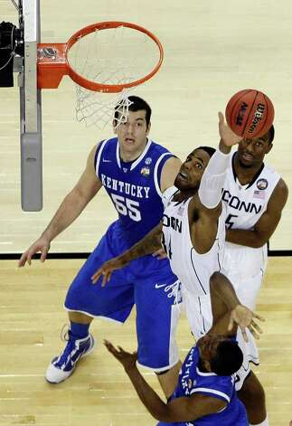 Connecticut center Alex Oriakhi (34) grabs a rebound over Kentucky forward Josh Harrellson (55) and Kentucky guard Brandon Knight (12) (below) during the second half of the NCAA National Semifinals at Reliant Stadium on Saturday, April 2, 2011, in Houston.  UConn defeated 56-55 and will play Butler in the National Championship game. ( Nick de la Torre / Houston Chronicle ) Photo: Nick De La Torre, Houston Chronicle For The Connecticut Post / Houston Chronicle for the Connecticut Post