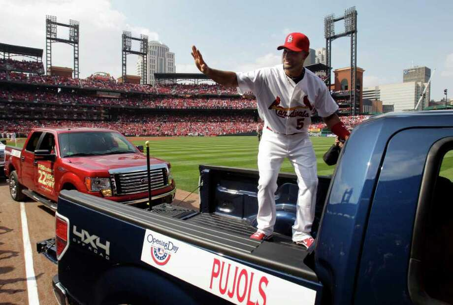 St. Louis Cardinals first baseman Albert Pujols waves to fans as he hops in the back of a pickup to be taken around the field for opening day ceremonies before the start of a baseball game against the San Diego Padres, Thursday, March 31, 2011, in St. Louis. (AP Photo/Jeff Roberson) Photo: Jeff Roberson