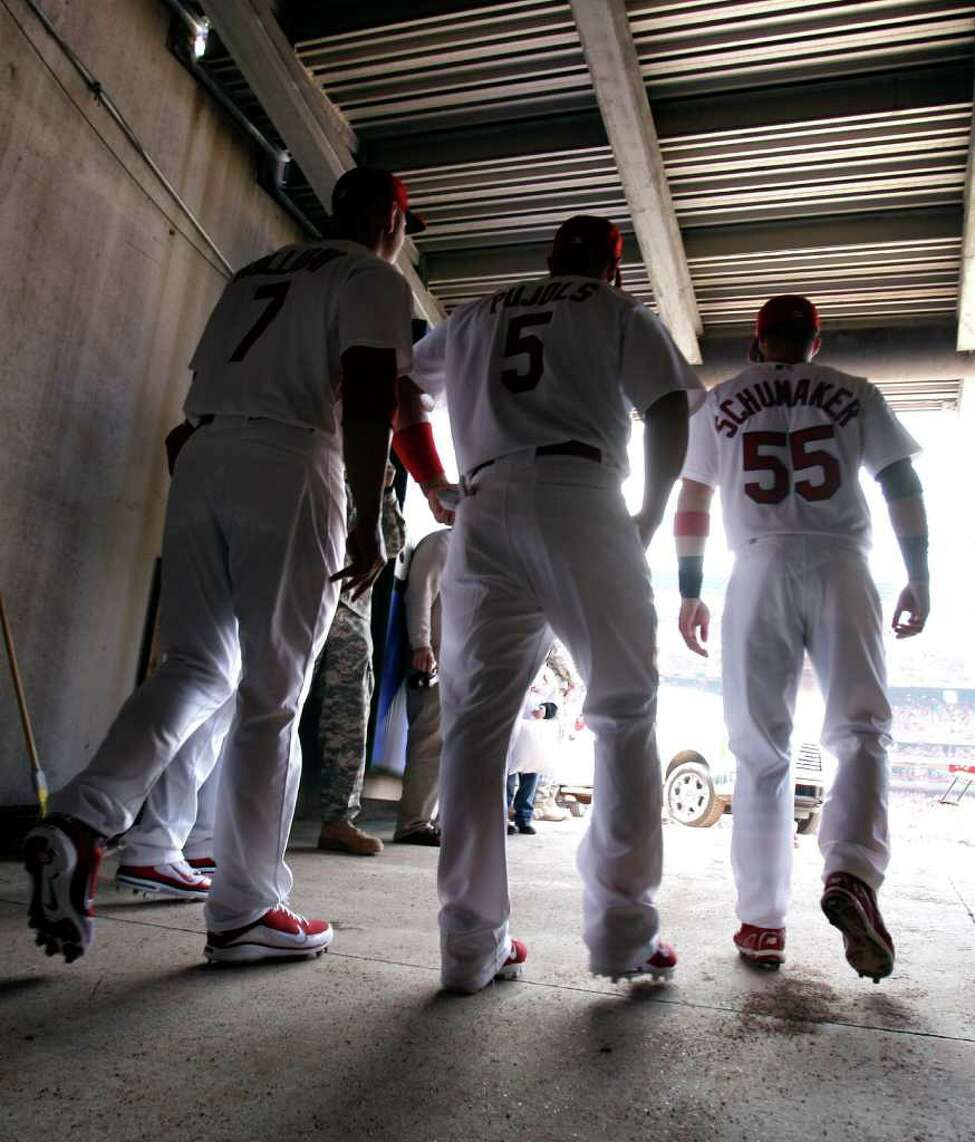 St. Louis Cardinals' Albert Pujols, center, walks out for opening day ceremonies with teammates Matt Holliday, left, and Skip Schumaker before the start of a baseball game against the San Diego Padres Thursday, March 31, 2011, in St. Louis. (AP Photo/Jeff Roberson)