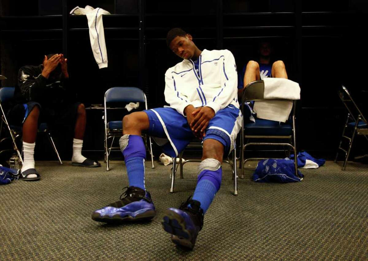 Kentucky guard DeAndre Liggins, center, who missed a crucial three point basket late in the game, sit in the locker room after the NCAA National Semifinals at Reliant Stadium on Saturday, April 2, 2011, in Houston. Connecticut won 56-55. At left is Kentucky guard Doron Lamb. ( Michael Paulsen / Houston Chronicle )