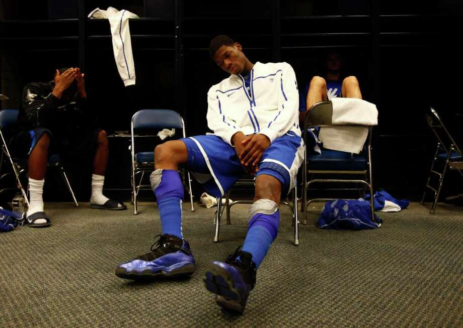 Kentucky guard DeAndre Liggins, center, who missed a crucial three point basket late in the game, sit in the locker room after the NCAA National Semifinals at Reliant Stadium on Saturday, April 2, 2011, in Houston.  Connecticut won 56-55.  At left is Kentucky guard Doron Lamb.  ( Michael Paulsen / Houston Chronicle ) Photo: Michael Paulsen, Houston Chronicle For The Connecticut Post / Houston Chronicle for the Connecticut Post