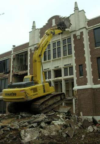 The Ambush Demolition excavator lines up to the front facade of the South Park Middle School as demolition began sometime around lunch on Good Friday.  Dave Ryan/The Enterprise / Beaumont