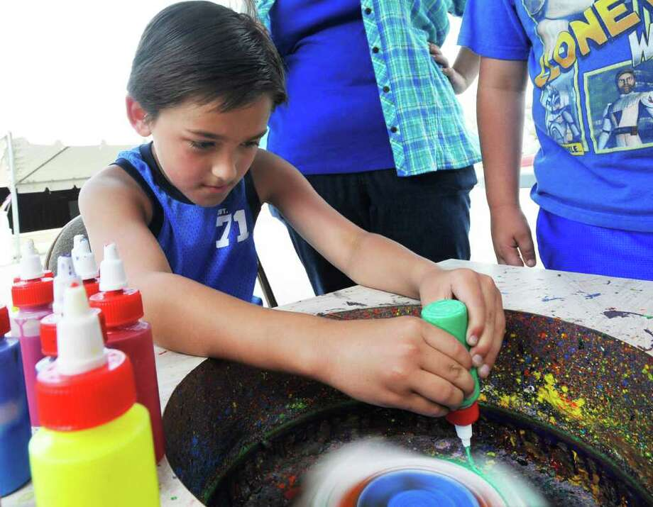 Daniel Dockens, 9, of Groves, works on creating a spin art painting at the First Baptist Church table during the first annual Groves Affair of the Arts event on Saturday.  Valentino Mauricio/The Enterprise Photo: Valentino Mauricio / Beaumont