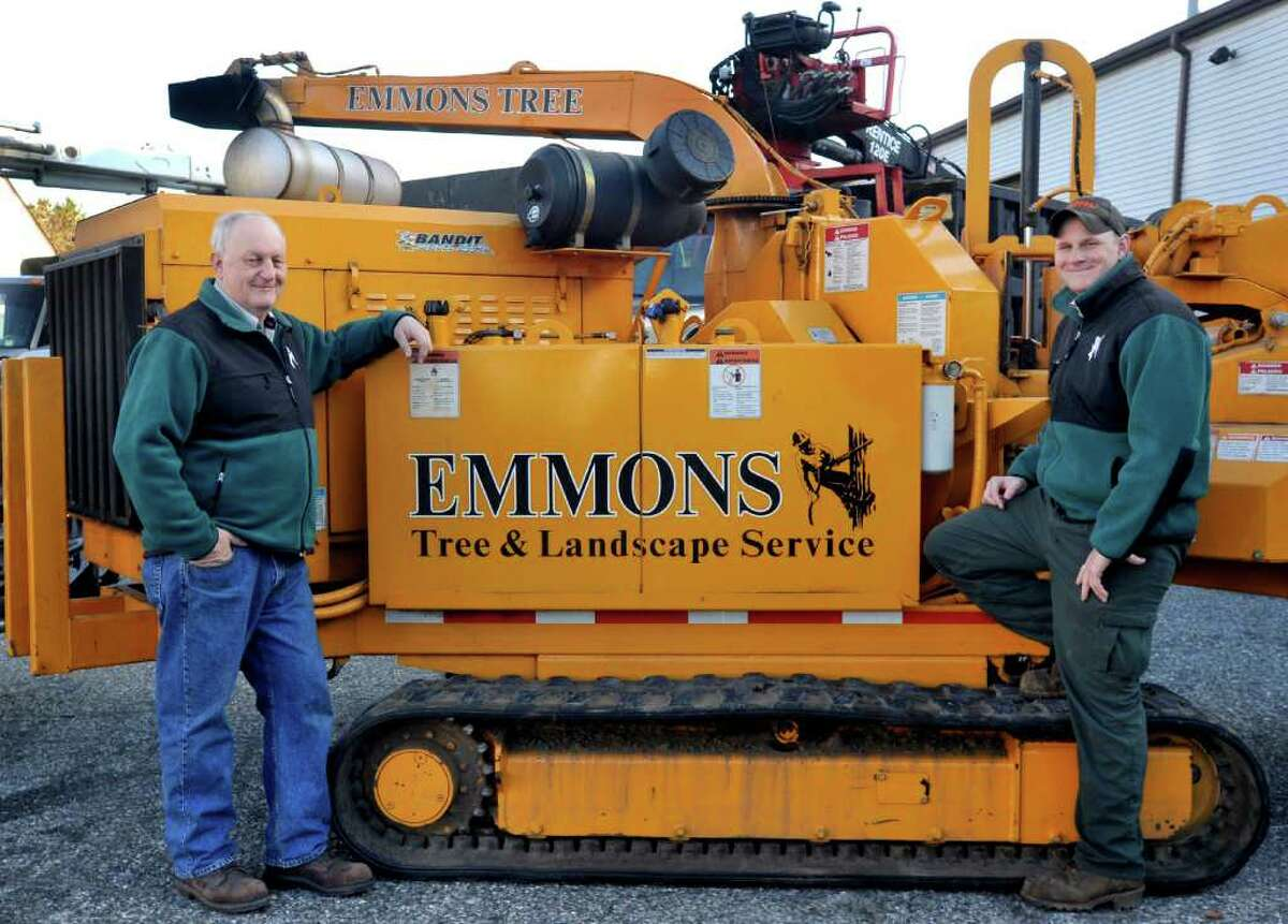 Rich Emmons, left, and Shawn Emmons, owner of Emmons Tree & Landscape Service stand with one of only two track chippers in the state. Photographed Saturday, April 2, 2011 outside their New Milford business.
