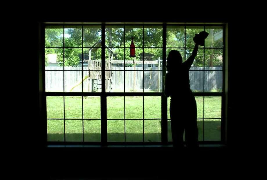 Kim Huch cleans the windows in her new home in Kountze. Tammy McKinley/The Enterprise Photo: TAMMY MCKINLEY / Beaumont