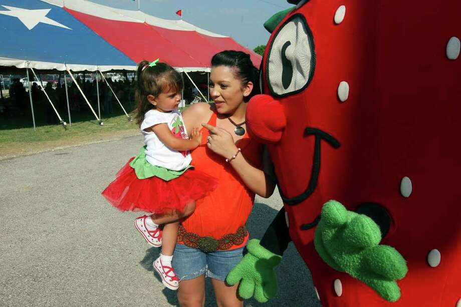FOR METRO - Michaela Stimpson, 2, (left) and her cousin Ashlee Messick talk with Freckles, the official mascot, Saturday April 2, 2011 during the 64th Annual Poteet Strawberry Festival in Poteet, Tx. PHOTO BY EDWARD A. ORNELAS/eaornelas@express-news.net) Photo: EDWARD A. ORNELAS, SAN ANTONIO EXPRESS-NEWS / SAN ANTONIO EXPRESS-NEWS NFS