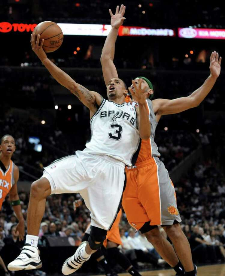 San Antonio Spurs guard George Hill is fouled by Phoenix Suns guard Jared Dudley on a shot during the second half of an NBA basketball game in San Antonio, Sunday, April 3, 2011. Hill had 29 points as the Spurs beat the Suns 114-97. Photo: AP