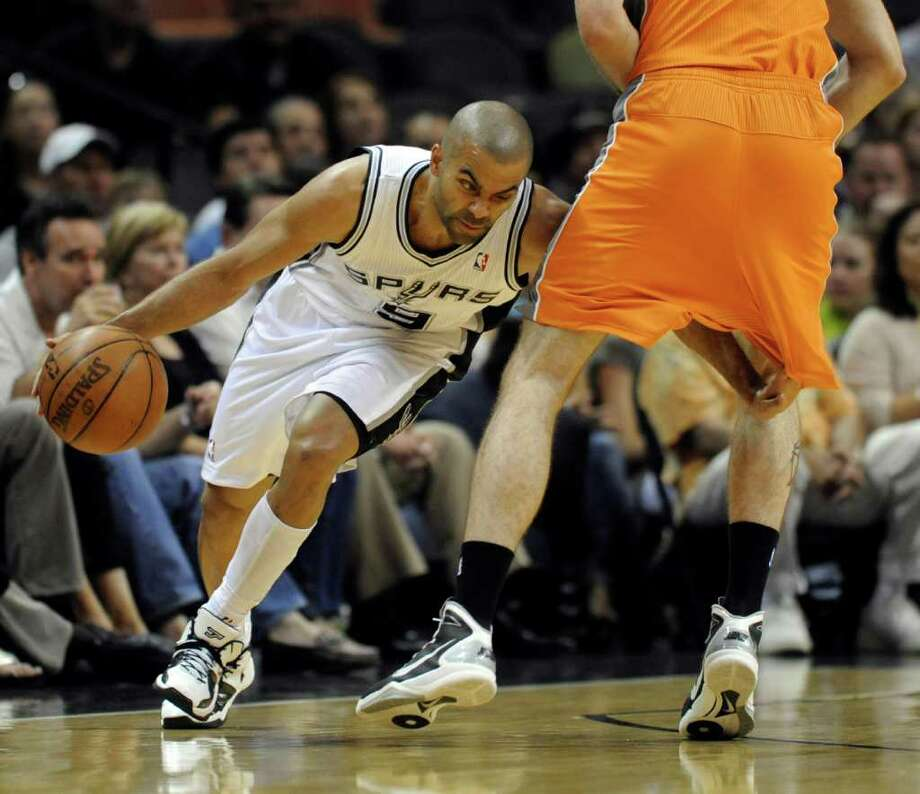 San Antonio Spurs guard Tony Parker, left, of France, drives around Phoenix Suns center Marcin Gortat, of Poland, during the first half of an NBA basketball game at the AT&T Center in San Antonio, Sunday, April 3, 2011. Photo: AP