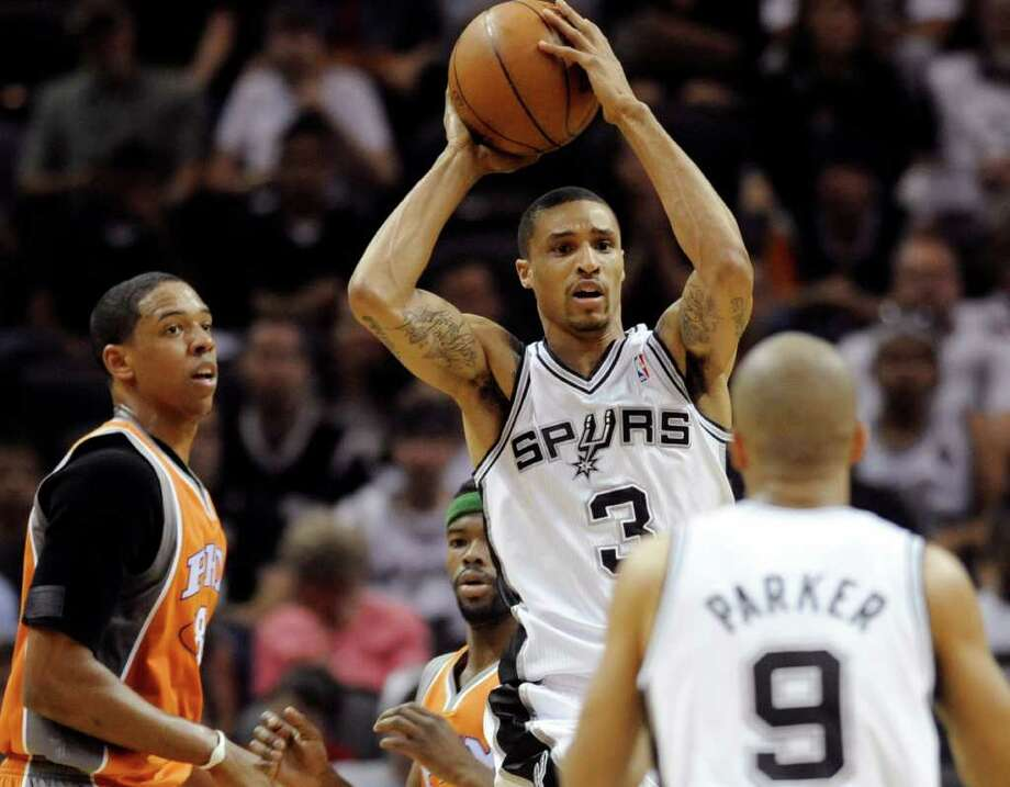 San Antonio Spurs guard George Hill (3) passes to teammate Tony Parker, of France, as he is defended by Phoenix Suns forward Channing Frye during the first half of an NBA basketball game at the AT&T Center in San Antonio, Sunday, April 3, 2011. Photo: AP