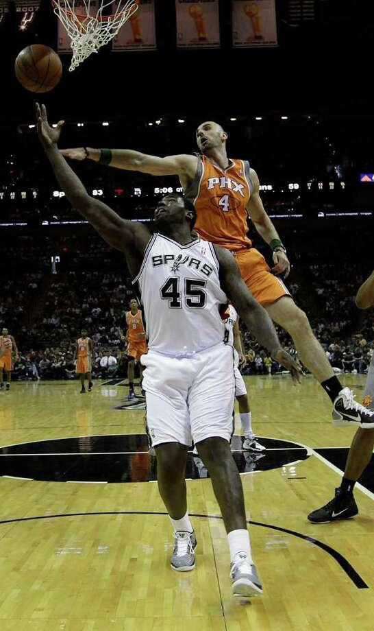 SPURS -- San Antonio Spurs DeJuan Blair goes under Phoenix Suns Marcin Gortat during the second half at the AT&T Center, Sunday, April 3, 2011. The Spurs won 114-97. JERRY LARA/glara@express-news.net Photo: JERRY LARA, San Antonio Express-News / SAN ANTONIO EXPRESS-NEWS (NFS)
