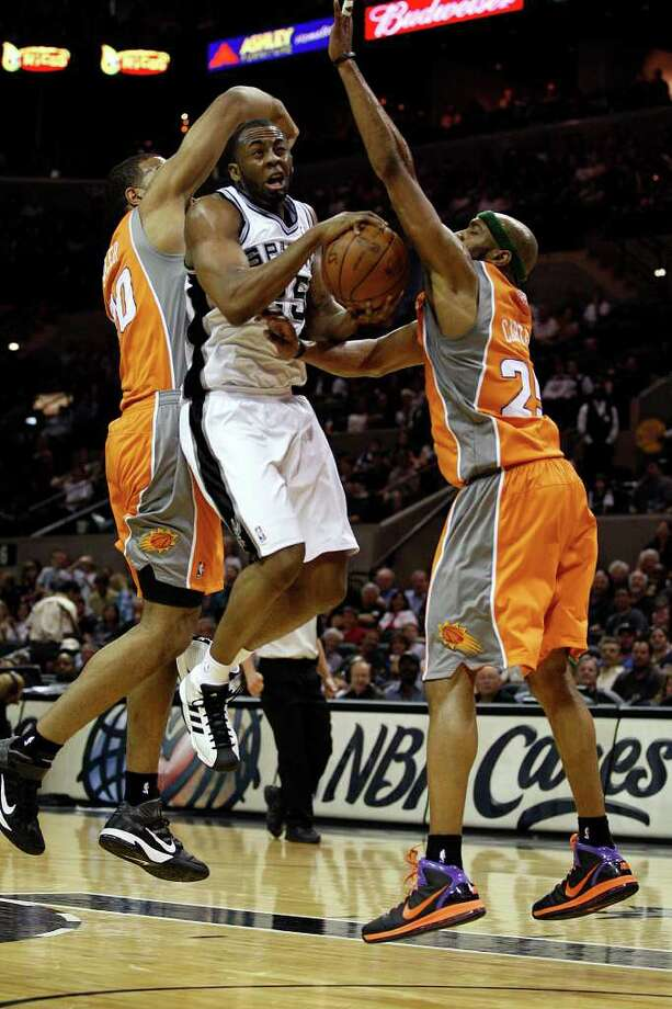 Spurs James Anderson drives to the goal under pressure from Phoenix Suns Garret Siler, left, and Vince Carter during the second half at the AT&T Center, Sunday, April 3, 2011. The Spurs won 114-97. JERRY LARA/glara@express-news.net / SAN ANTONIO EXPRESS-NEWS (NFS)
