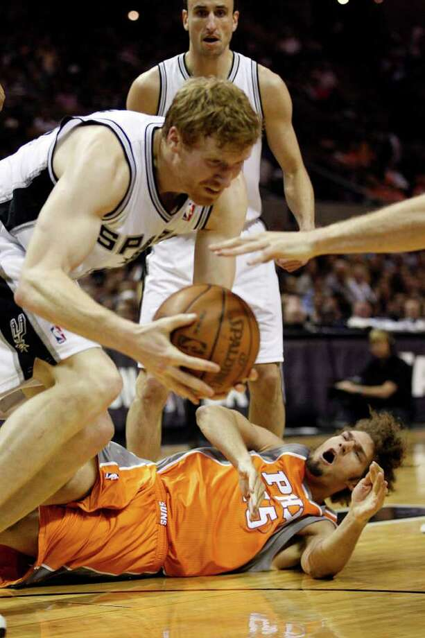 Phoenix Suns Robin Lopez hits the floor hard as he is beaten to a rebound by  Spurs Matt Bonner during the first half at the AT&T Center, Sunday, April 3, 2011. Bonner ended up with 16 points and 11 rebounds. JERRY LARA/glara@express-news.net / SAN ANTONIO EXPRESS-NEWS (NFS)