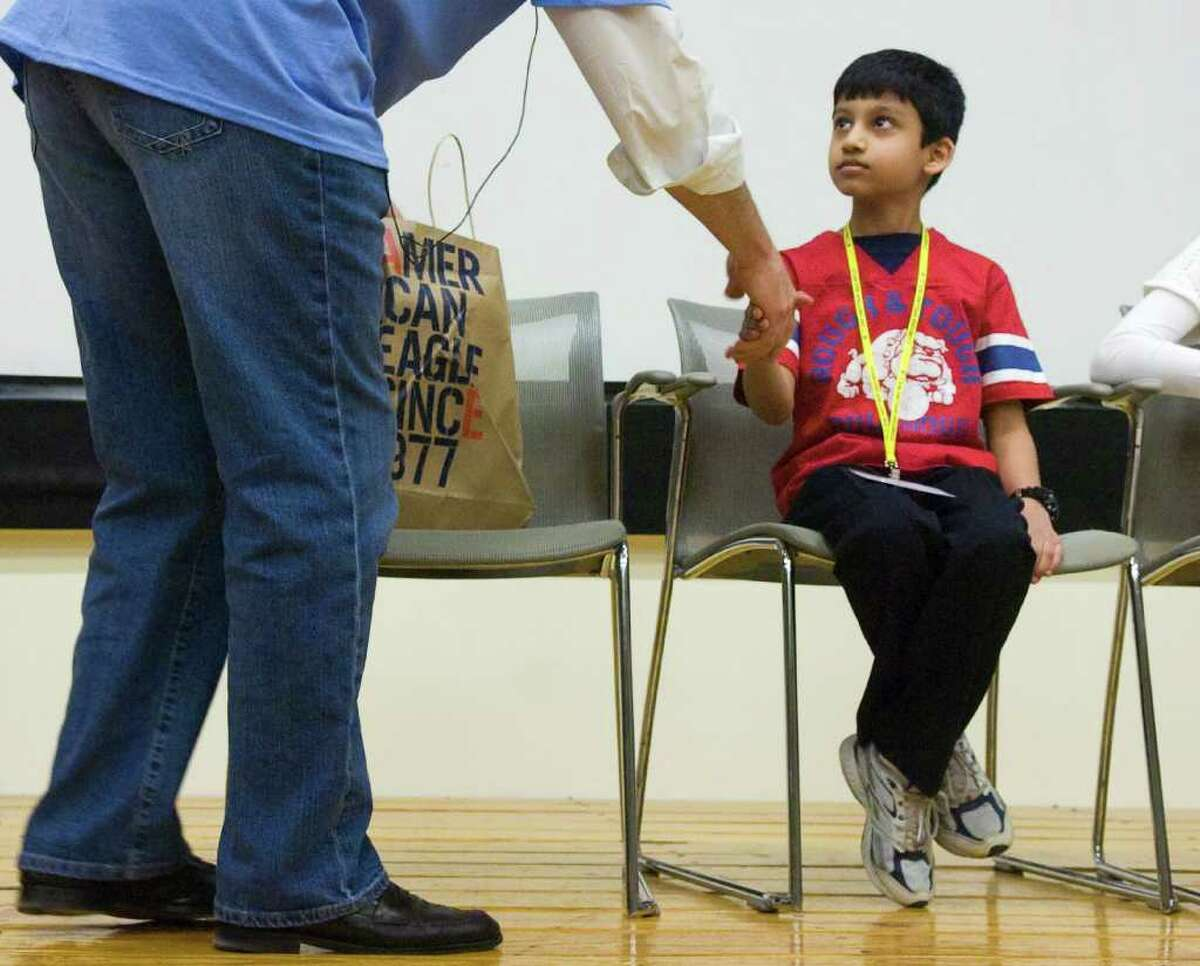 Fourth grader Harsha Kolachina is congratulated after winning the First Annual Stamford Spelling Bee at the Ferguson Library in Stamford, Conn., April 3, 2011.