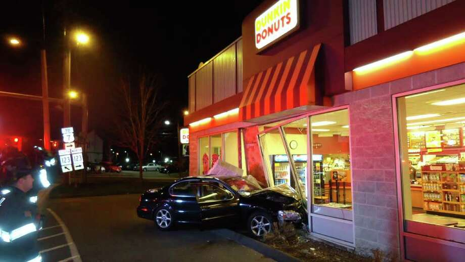 The Norwalk Fire Department responded to a car into a building this morning just after 2:30 am. Two patrons sitting at a table inside the Dunkin Donuts, located at 195 Main Avenue Norwalk were struck and thrown across the floor when the car hit the building. The Nissan Maxima's left front tire came to rest at the spot where the patrons table was located. Photo: Connecticut Post Contributed / Connecticut Post contributed
