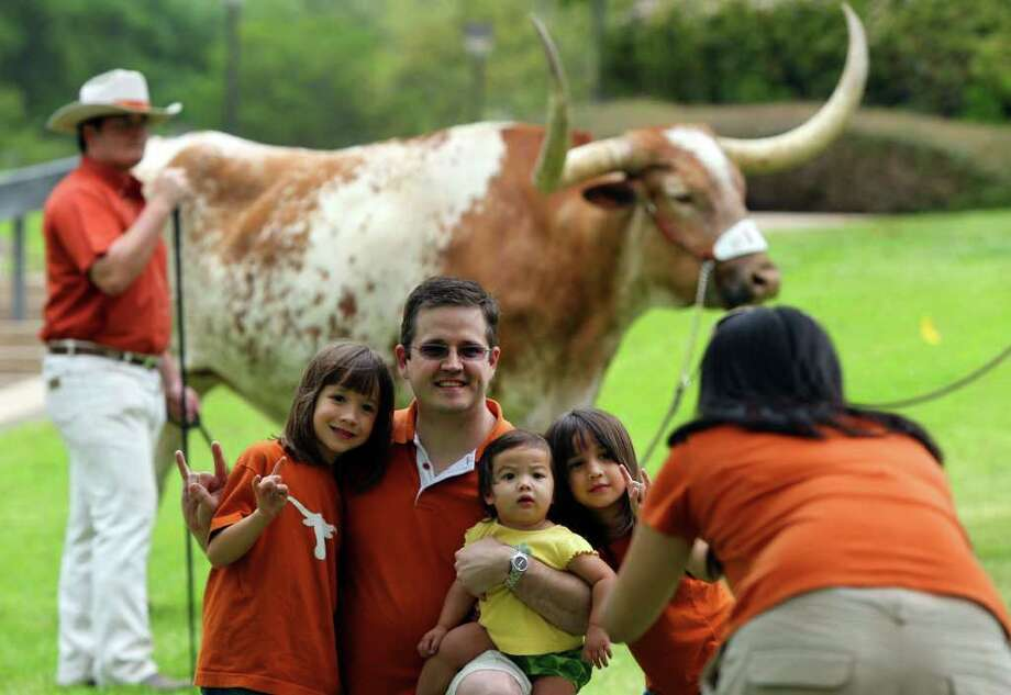 Chris Cloteaux (center) poses for a family portrait as his wife Tuanh (cq) Cloteaux (facing away, right) takes a picture Sunday April 3, 2011 at the north end of Darrell K. Royal-Texas Memorial Stadium in front of University of Texas Longhorn mascot Bevo XIV before the annual spring scrimmage football game in Austin. On the left is Elizabeth Cloteaux,6, seated (yellow shirt) is Grace Cloteaux,1, and to the right of Grace is Catherine Cloteaux,5. JOHN DAVENPORT/jdavenport@express-news.net Photo: SAN ANTONIO EXPRESS-NEWS