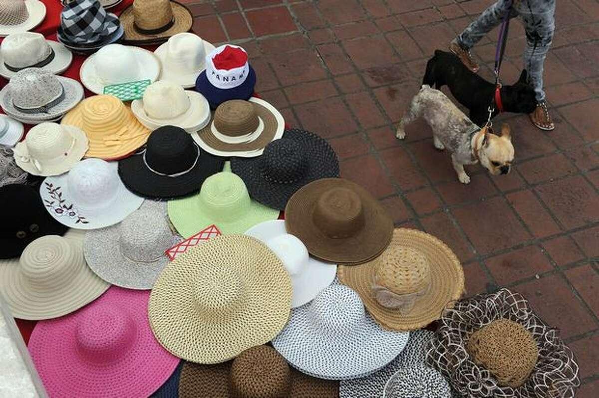 A Panamanian woman passes with her dogs in front of a stand selling hats in the historic downtown area of Panama City on January 19, 2011.