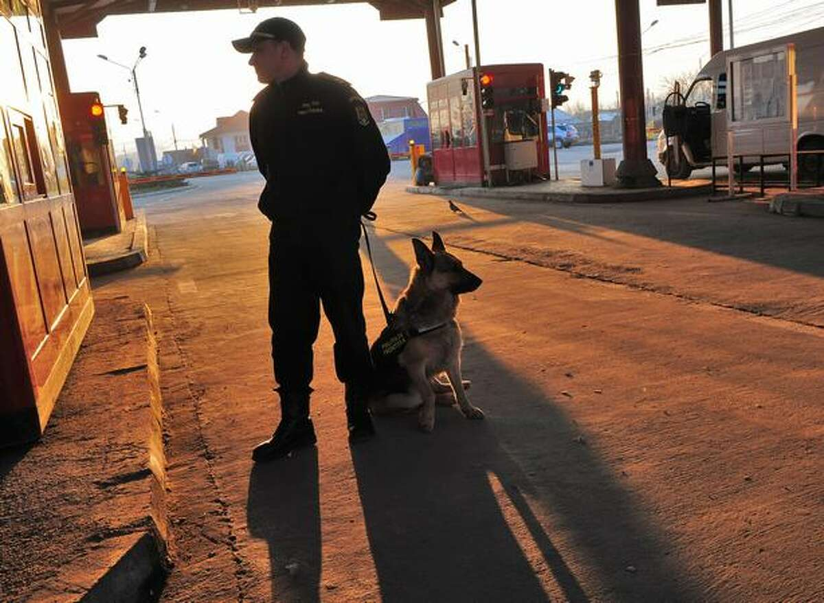 A Romanian border police officer and his dog stand at the Sculeni border crossing point to the Republic of Moldova on January 18, 2011. Romania and Bulgaria, the two most recent members of the European Union, have declared Schengen accession as a national priority this year, but Bucharest and Sofia look set to fail in their membership bids in March, with France and Germany publicly opposing such a move.