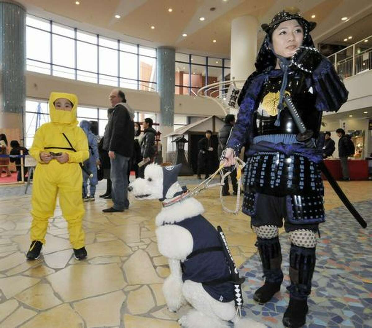 A dog dressed like a ninja is led by a woman dressed in a samurai costume as a girl dressed in a ninja costume looks on during a festival at a shopping mall in Tokyo on February 5, 2011. Some 80 people in ninja costumes from the city of Iga in Mie Prefecture held the event to promote tourism in Iga, which hosts a ninja museum as well as an annual ninja festival. A ninja was an assassin or spy in feudal Japan (circa 15th century), usually trained for stealth, espionage and other unorthodox arts of war.