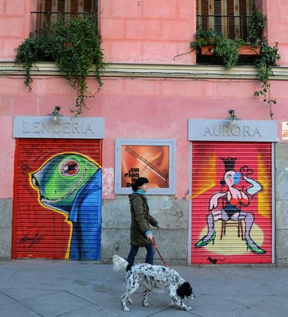 A woman walks her dog past graffiti on shopkeepers' shutters on February 8, 2011 in Madrid. The Spanish capital has invited graffiti artists to paint the steel shutters protecting their stores at night in the hope this will stop them from being defaced by crude scribblings made on the run. Over 130 graffiti artists from across Europe, including Bristol and Milan, decorated 140 shutters on February 6, 2011 in Madrid's central Malasana neighborhood, which has long been the heart of the city's counter-cultural scene.