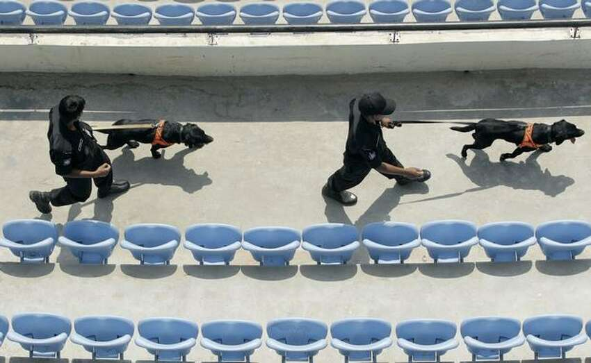 Bangladesh's special task force officers with sniffer dogs perform security checks at the Sher-E-Bangla National Stadium in Dhaka, Bangladesh,Thursday March 3, 2011. Bangladesh played West Indies in the Cricket World Cup Group B match Friday.(AP Photo/ Themba Hadebe)
