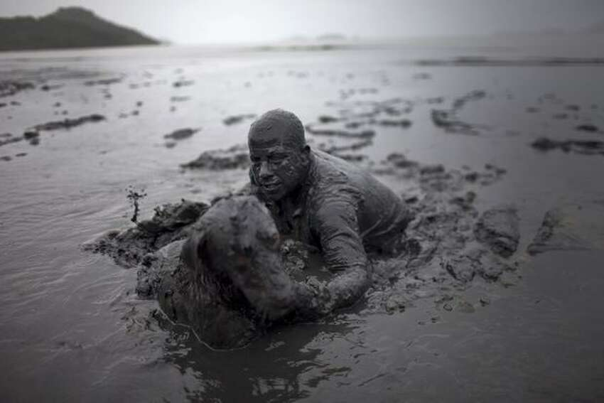 A man and his dog walk out after covering in mud as part of the