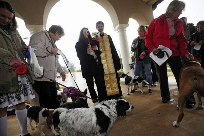Athena Andris (center) and Father Anthony Salzman are surrounded by dogs after a Blessing of the Pets at St. Philothea Greek Orthodox Church on Saturday, March 5, 2011, in Watkinsville, Ga. (AP Photo/Athens Banner-Herald, David Manning)