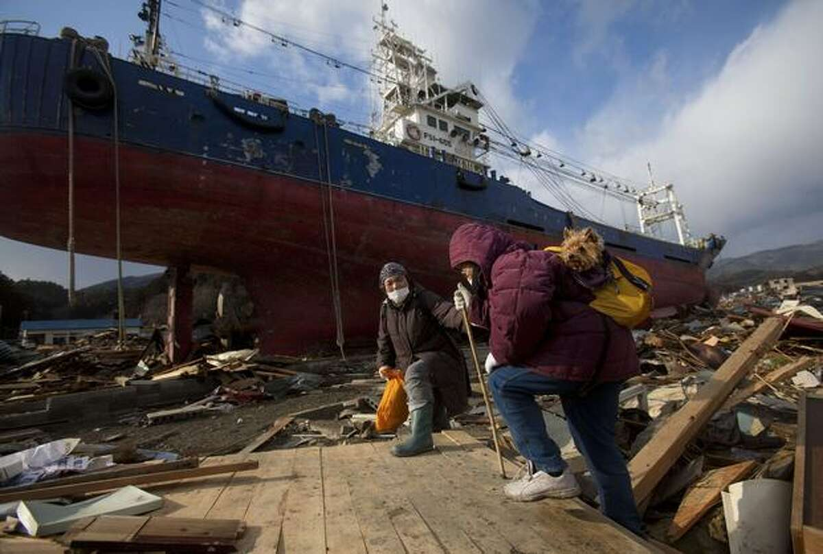 Two elderly Japanese women and a pet dog pass by a ship that washed into their neighborhood by the tsunami as they try to make their way to search for their destroyed home in the leveled city of Kesennuma, in northeastern Japan, Thursday March 17, 2011. (AP Photo/David Guttenfelder)