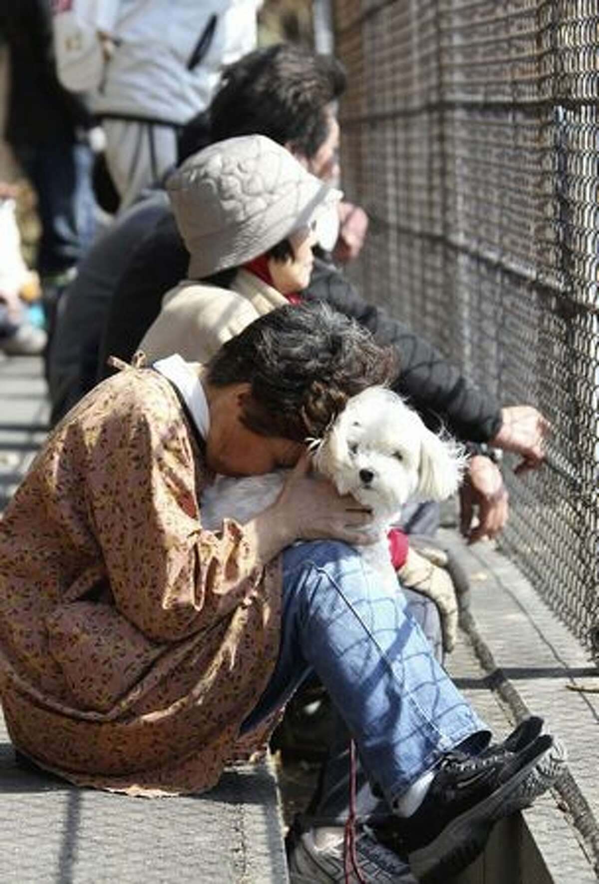 A woman holding her dog reacts after evacuating following a tsunami warning in Kamaishi, Iwate Prefecture, northern Japan, Monday, March 14, 2011, three days after a powerful earthquake-triggered tsunami hit the country's east coast. (AP Photo/The Yomiuri Shimbun, Daisuke Uragami)
