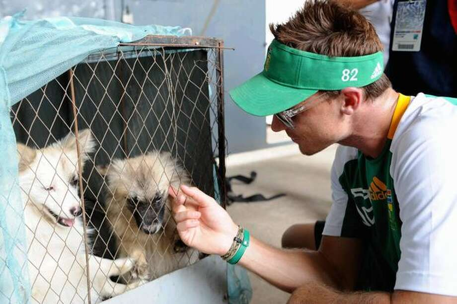 Dale Steyn of South Africa plays with a puppy during a South Africa nets session at SBNCS Stadium on March 24, 2011 in Dhaka, Bangladesh. Photo: Getty Images / Getty Images