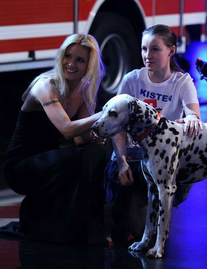"Swiss co-presenter Michelle Hunziker (left) kneels next to a Dalmatian dog during the German TV game show ""Wetten Dass...?"" (Let's make a bet) in Augsburg, Germany, on March 19, 2011. Photo: Getty Images / Getty Images"