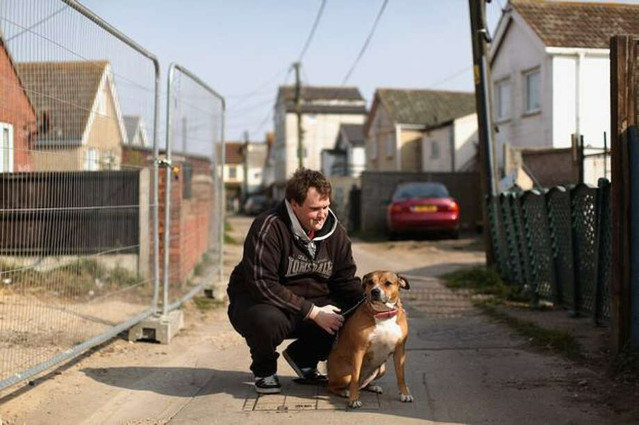 A man crouches with his dog in the town of Jaywick, which has been named as the most deprived place in England, on March 25, 2011. The study, which is based on the Index of Multiple Deprivation, considered various indicators of deprivation including: unemployment, health and quality of housing. Photo: Getty Images / Getty Images