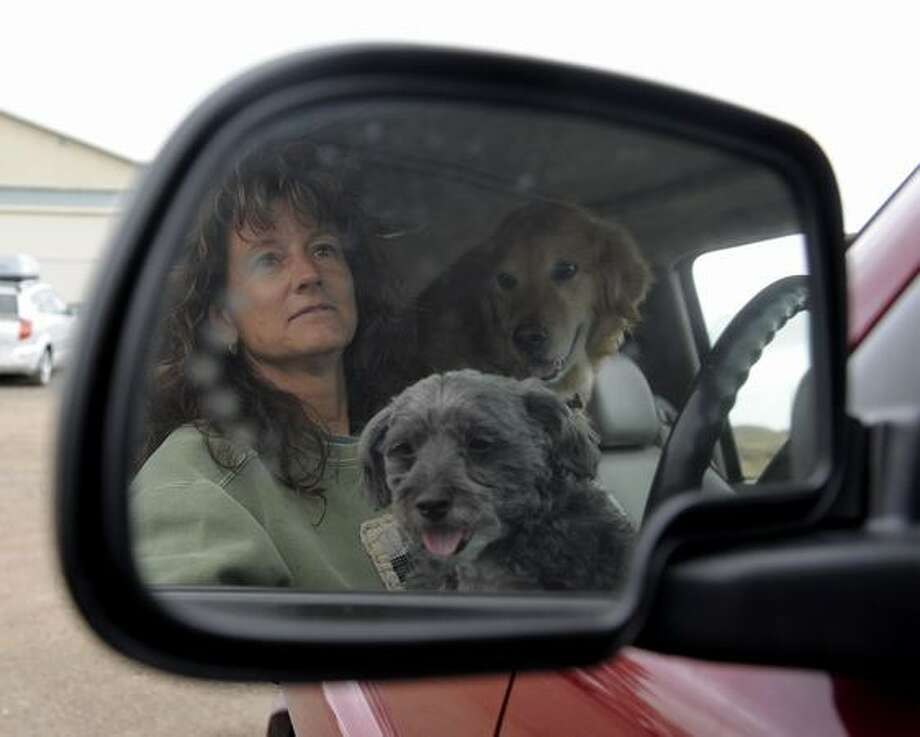 Kit Harmon patiently waits in her car with her dogs after she evacuated her house due to the fire near Ponderosa High School in Parker, Colo., Thursday, March 24, 2011. Residents near the fire were evacuated to the Kirk Hall at the Douglas County Fairgrounds. (AP Photo/The Denver Post, John Leyba) Photo: Associated Press / Associated Press